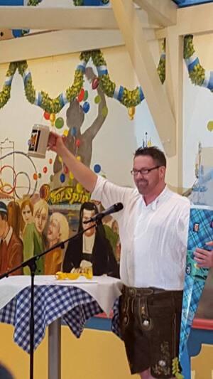 André Hartmann mit dem neuen Maßkrug, © Oktoberfest: Kabarettist André Hartmann stellt Wiesn-Maßkrug vor