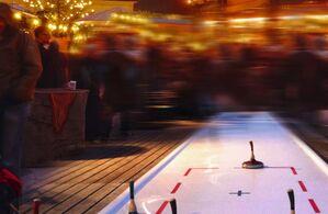 eisstockschießbahn auf weihnachtsmarkt am chinesischen turm mit leuten und lichtern im hintergrund, © Eisstockbahn am Weihnachtsmarkt am Chinesischen Turm