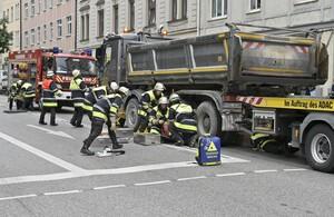 Einsatzkräfte der Feuerwehr, retten Frau unter Laster, © Feuerwehr München