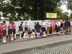 wartende Menschen vor dem Zaun um die Theresienwiese