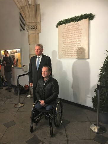 Oberbürgermeister Dieter Reiter und Überlebender Dimitrios Lagkadinos vor der Gedanktafel im Rathaus