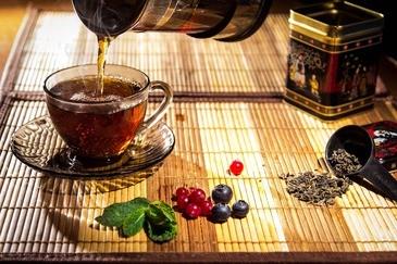 Tee wird in eine Tasse geschenkt