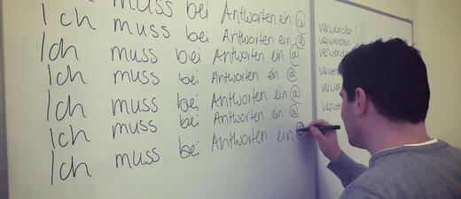 Polizei beamter an Tafel und schreibt ich muss bei antworten ein @ verwenden, © Polizei München