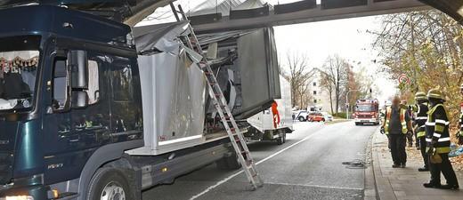 Ein kaputter LKW steckt in einer Unterführung fest, daneben stehen Feuerwehrleute, © Berufsfeuerwehr München