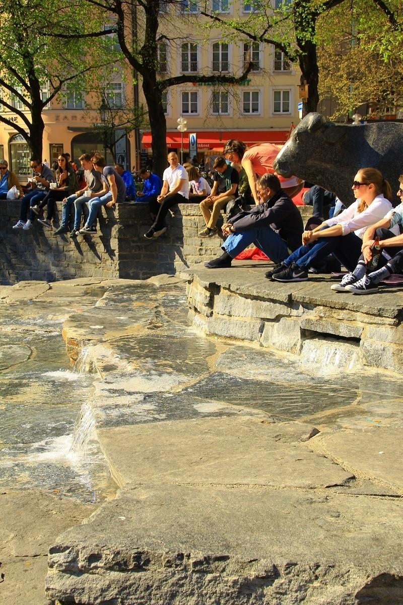 Menschen erholen sich am Rindermarktbrunnen