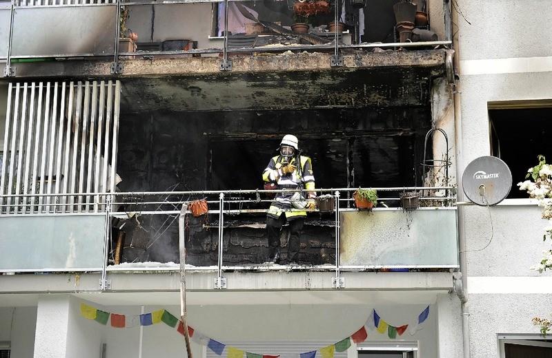 Ein Münchner Feuerwehrmann steht erschöpft auf dem Balkon des verbrannten Hauses, © Erschöpft nach dem Brand: Ein Münchner Feuerwehrmann Foto: Berufsfeuerwehr München