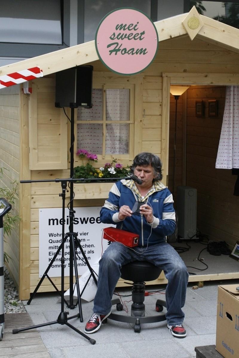 Tommy Schmidt beim Musizieren vor seinem Gartenhäuschen, © Foto: Serviceplan