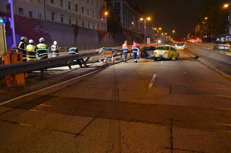 Unfall Mittlerer Ring, Knautschzone des schwarzen Mercedes komplett kaputt, gelber BMW von hinten zu sehen, linke Seite von aufprall auf Mercedes geschädigt, Mittelleitplanke beschädigt, Feuerwehrmänner an der Unfallstelle zu sehen, Totalaufnahme des Unfallortes., © Foto: Polizei