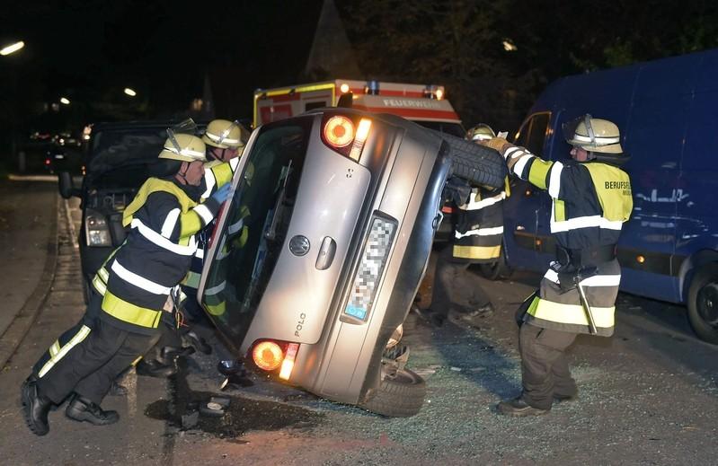 Helfer der Feuerwehr kippen den Unfallwagen wieder auf die Räder, © Feuerwehr München