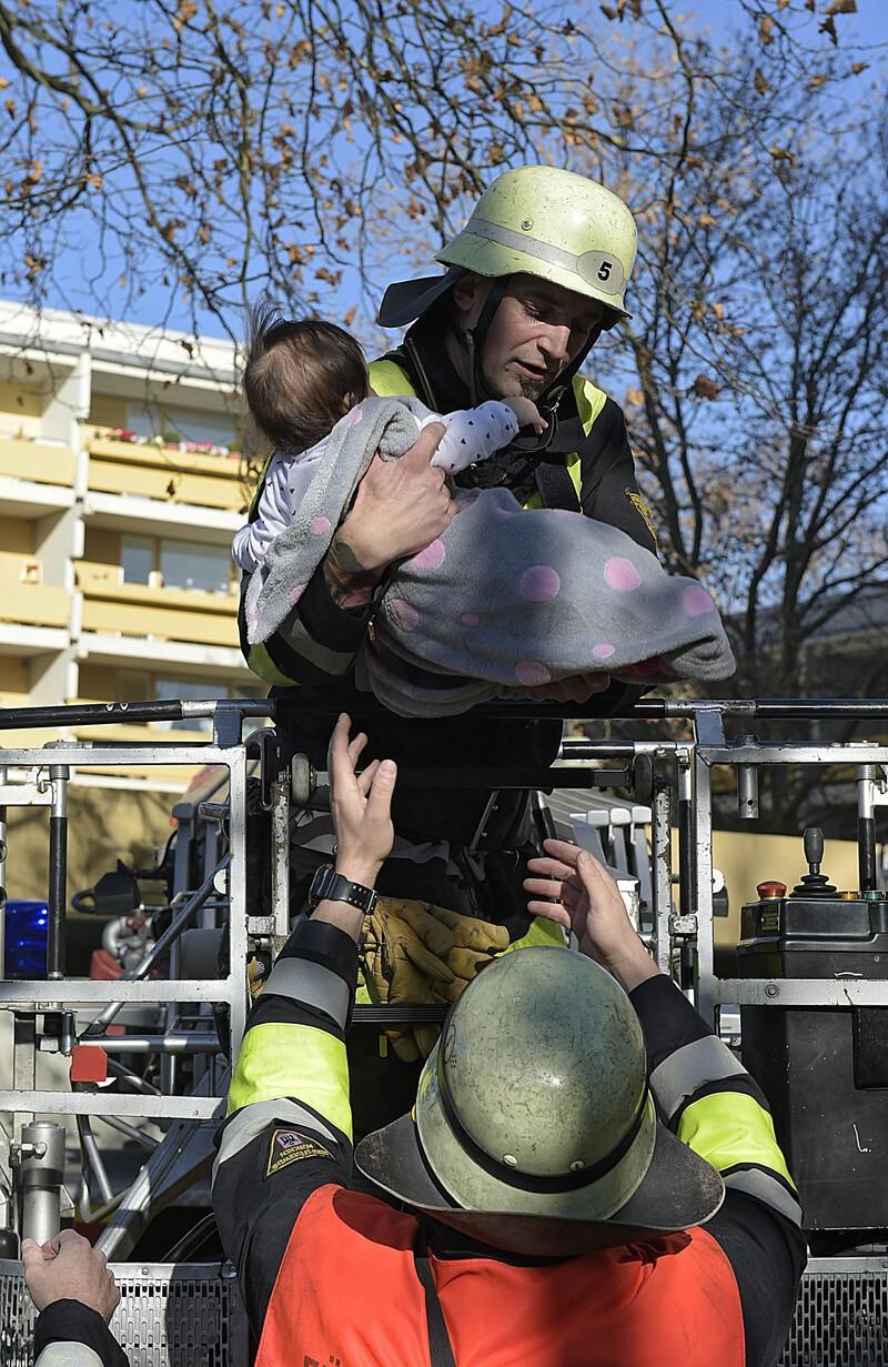 Ein Feuerwehrmann bring ein Baby in Sicherheit, © Foto: Berufsfeuerwehr München
