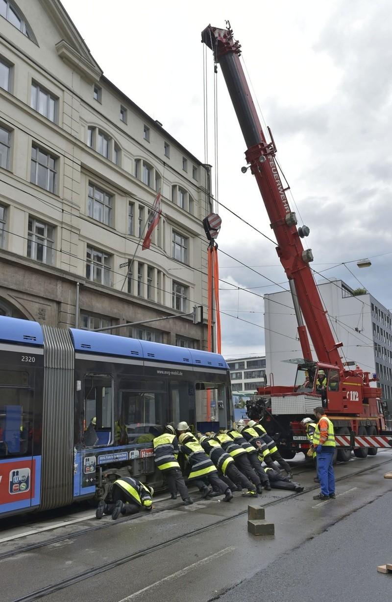 Feuerwehr Männer versuchen mit Hilfe eines roten Krans die entgleiste Trambahn wieder in die Gleise zu drücken, © Feuerwehr München