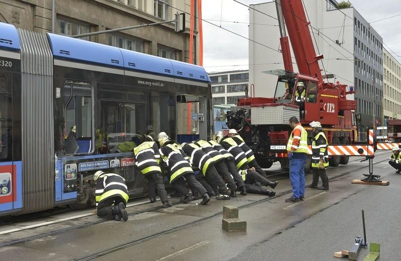 Feuerwehrmänner drücken seitlich gegen Trambahn mit Kran, © Feuerwehr München