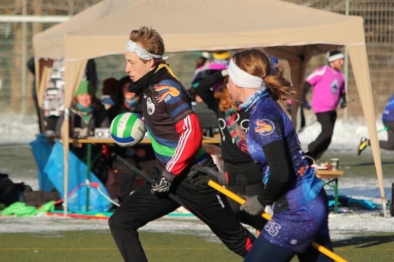 Zwei Quidditchspieler auf Spielfeld bei Winterspielen beim Rennen mit dem Ball und auf Besen, © Deutscher Quidditchbund/ Nick van Klaveren