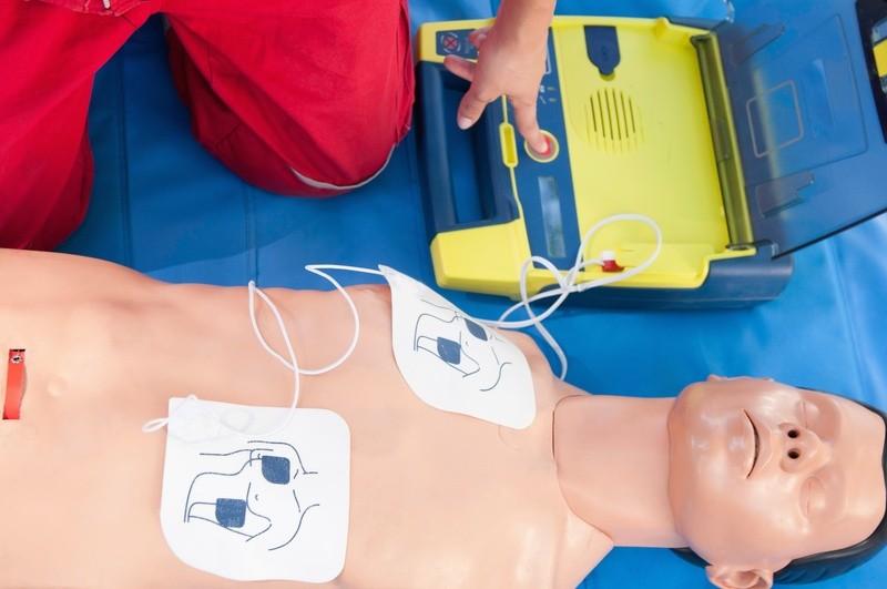 Puppe mit Auto-Defibrillator, © Auto-Defibrillatoren merken nicht nur selbstständig, ob die Elektroden an der richtigen Stelle sitzen, sondern geben dem Bediener auch alle Kommandos. fotolia.com ©  Microgen
