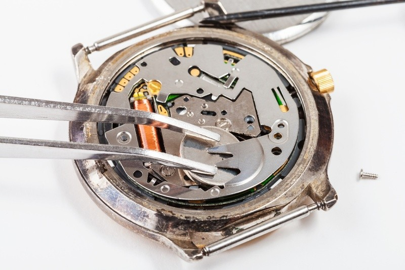 Uhrwerk mit Pinzette in der Bearbeitung., © Seit den 1980ern kommen Quarzuhren auf mehrjährige Laufzeiten mit nur einer Batteriefüllung - und bleiben während der ganzen Zeit gleich genau. fotolia.com ©  woe