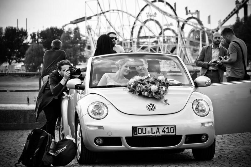 """© Der Hochzeitsfotograf fotografiert das Brautpaar vor der Achterbahn """"Olympia Looping"""" auf der Wiesn."""