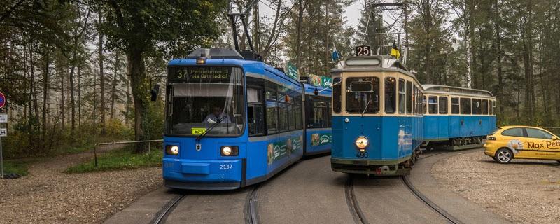 Eine moderne und eine alte Trambahn, die in München nebeneinander fahren.