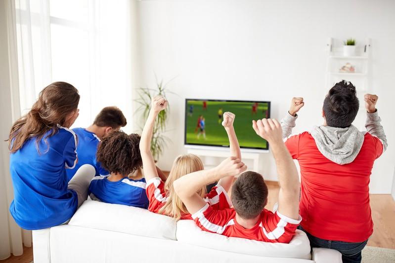 Familie beim Fußballschauen am Fernseher, © Die Sportberichterstattung stellt sicherlich den Bereich des Programms dar, der sich mit Aufkommen des Privatfernsehens am deutlichsten verändert hat. fotolia.de © Syda Productions (#191058717)