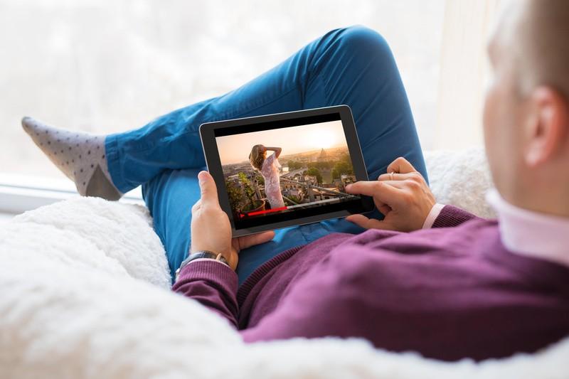 """Tablet, Mann, © Das """"Fernsehen"""" der Zukunft – so kann es aussehen: Streaming auf mobilen Endgeräten, je nach Lust und Laune, wann und was geschaut wird. Ist das klassische Fernsehen tot? fotolia.de © Kaspars Grinvalds (#210134411)"""