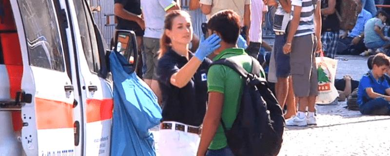 Eine Helferin des Bayerischen Roten Kreuzes untersucht einen angekommenen Flüchtling
