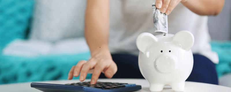 Sparschwein steht auf Tisch und wird mit Geld gefüttert, © Foto:  Africa Studio – 410140204 / Shutterstock.com