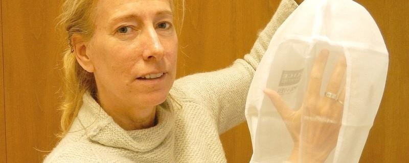 Die Sprecherin des Bremer Innensenators Rose Gerdts-Schiffler führt die neue Spuckschutzhaube vor., © Die Sprecherin des Bremer Innensenators Rose Gerdts-Schiffler führt die neue Spuckschutzhaube vor.