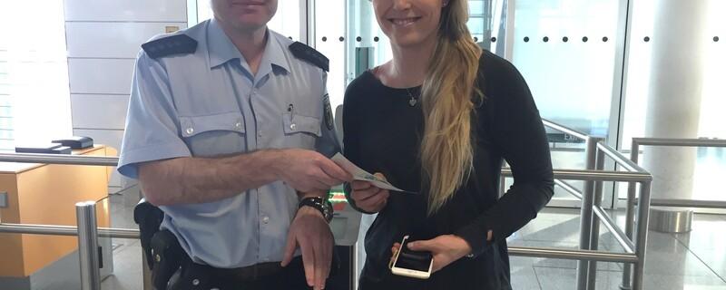 Ein Bundespolizist übergibt Lindsey Vonn am Münchner Flughafen einen Notreiseausweis, © Ein Bundespolizist übergibt Lindsey Vonn am Münchner Flughafen einen Notreiseausweis. Bild: Bundespolizei