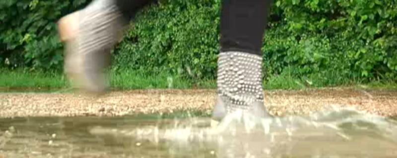 Frau rennt bei Regen durch eine Pfütze