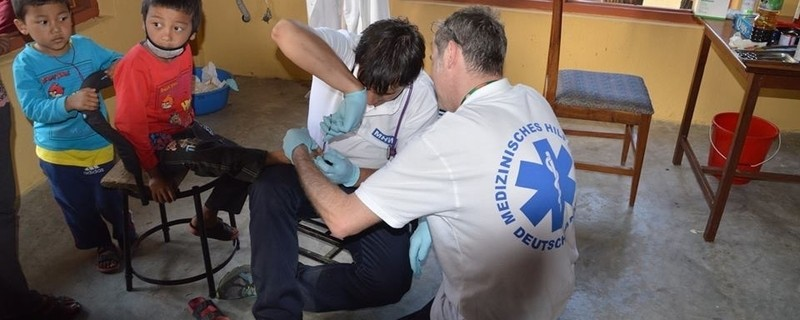 Ein Helfer kümmert sich um vom Erdbeben verletzte Kinder in Nepal, © Die Helfer in Nepal haben vor Ort alle Hände voll zu tun Foto: MHW