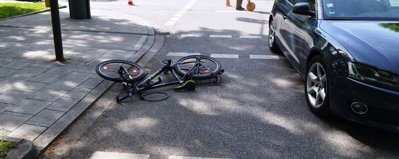 Symbolfoto eines Fahrradunfalls mit einem Auto, Polizist im Hintergrund, © Symbolfoto
