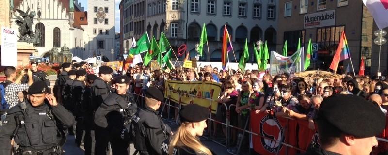 """Polizisten stehen vor der Absperrung, dahinter demonstriert das Bündnis """"München ist Bunt"""", © Die Gegendemonstranten waren klar in der Mehrheit Foto: Red"""