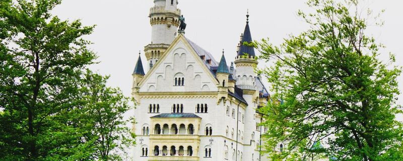 Schloss Neuschwanstein Disneyland Vorbild, © Das Schloss Neuschwanstein in Mitten von Grün - Foto:  Dirk Schiff/Portraitiert.de