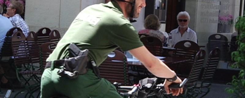 Ein uniformierter Polizist auf einem Fahrrad, © Seit 10 Jahren führt die Münchner Polizei mittlerweile Kinderpräventionsfahrten (Radlprüfungen) an Grundschulen durch.
