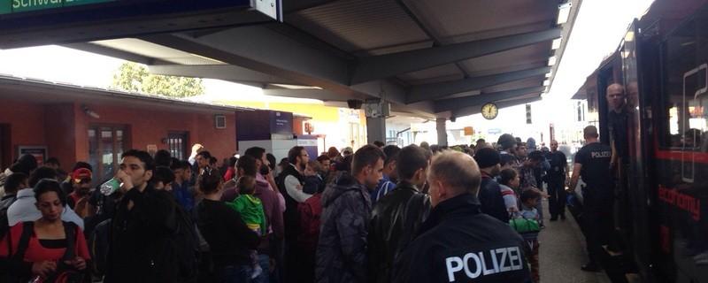 Am Bahnhof in Freilassing stehen eben angekommene Flüchtlinge