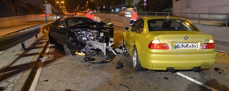 nahe Aufnahme der geschädigten Autos, Knautschzone des schwarzen Mercedes komplett demoliert, gelber BMW vorne links beschädigt, von hinten zu sehen, Autoteile auf der Straße verteilt., © Foto: Polizei