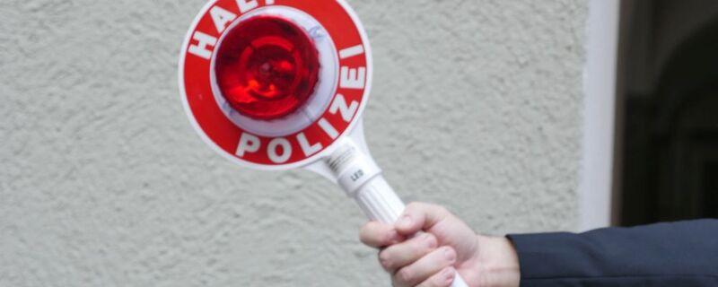 Halt Polizei schild rot weiß in hand gehalten vor grauer wand