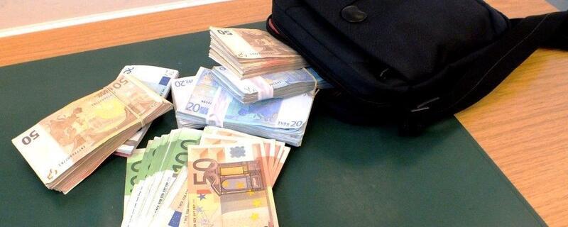Geldbündel liegen auf dem Tisch neben einer Tasche, © Foto: Bundespolizei München