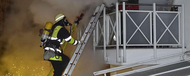 feuerwehrmann auf leiter mit atemschutzmaske vor balkon einer brennenden Wohnung mit viel Qualm und Rauch, © Berufsfeuerwehr München