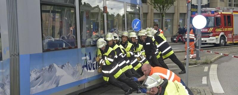 Feuerwehrmänner schieben seitlich Trambahn wieder in die Gleise, © Feuerwehr München