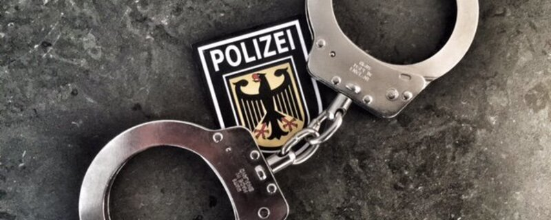 Handschellen vor einem Bundespolizei-Wappen, © Symbolfoto