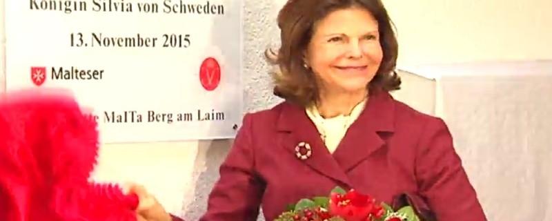 Königin Silvia enthüllt Maltaeserhaus mit Blumenstrauß und rotem jacket, © Königin Silvia zu Besuch in München