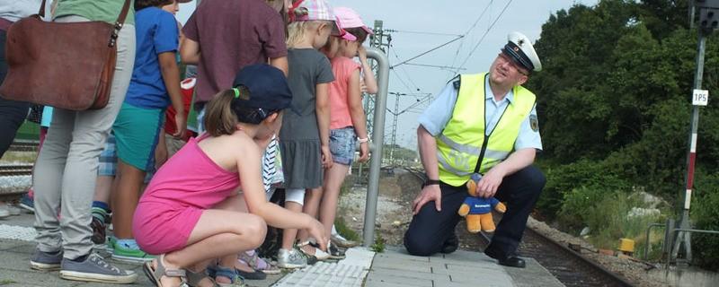 Ein Bundespolizist erklärt Kindern, wie man sich an Bahngleisen richtig verhält., © Foto: Bundespolizei