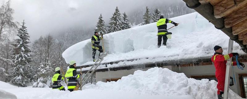 Einstazkräfte der Feuerwehr räumen den vielen Schnee von einem Hausdach, © Berufsfeuerwehr München