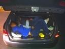 Flüchtlinge zusammengekauert in einem Schleuser-Kofferraum