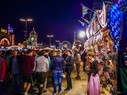 Oktoberfestbesucher schlendern am Abend über die Festwiese