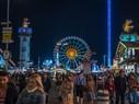 Riesenrad und Skyfall-Tower glänzen bei Nacht, © Der Ausblick aufs Münchner Oktoberfest - Die Wirtsbudenstraße auf der Wiesn